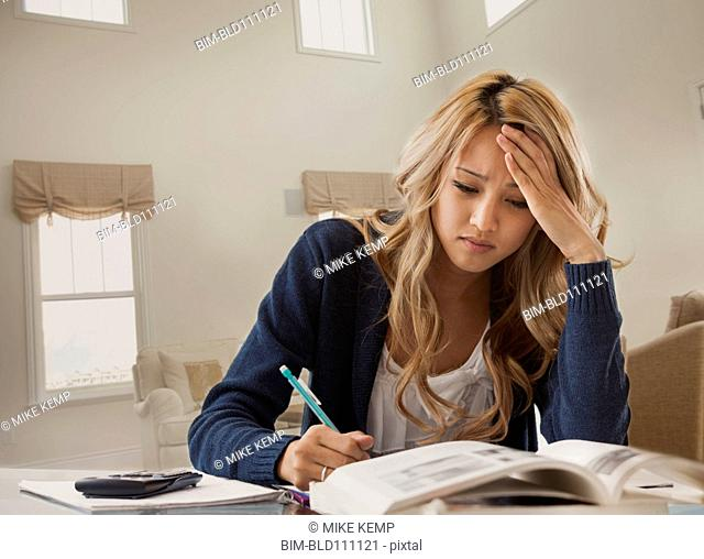 Anxious mixed race woman studying