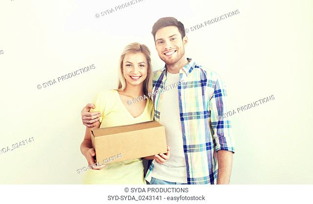 smiling couple with box moving to new home