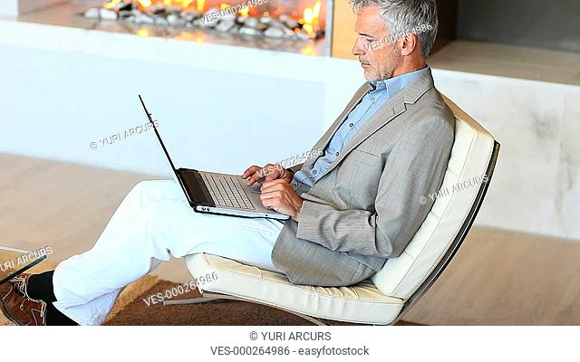 An attractive senior executive sitting and typing on his laptop at home