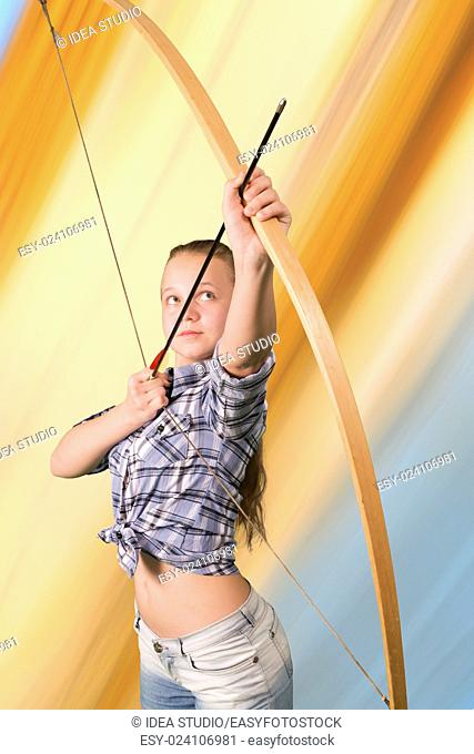 Teen girl practicing archery standing on abstract background