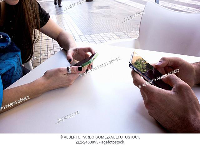 Couple using the phone on the table, valencia, Spain
