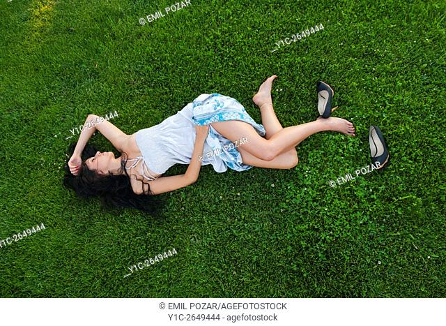 Lying on meadow detached high-heels shoes