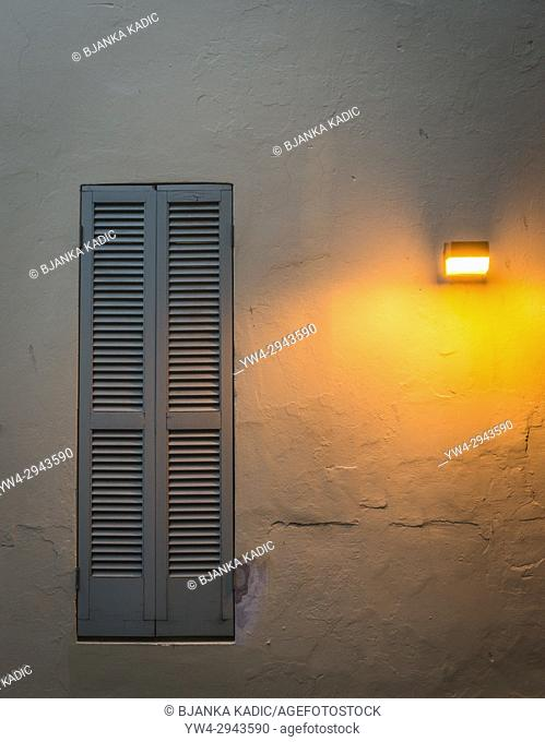 Venetian blind window imbedded in a worn wall and yellow wall light