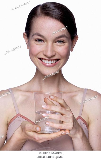 Happy portrait of young woman with glass of water