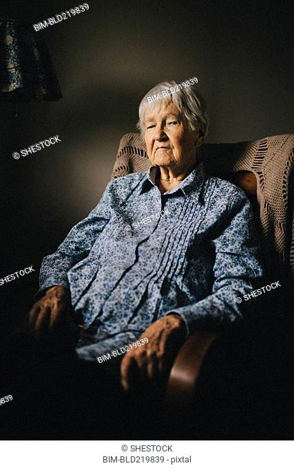 Older mixed race woman sitting in armchair