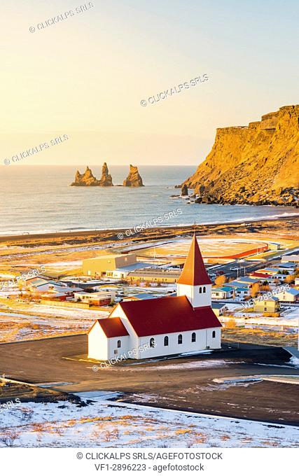 Vik i Myrdal, Southern Iceland, Iceland. High angle view over Vik's church, the village, and the Reynisdrangar rocks at sunrise