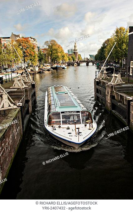 Canal boat passing the Sint Antoniesluis sluice gates with the Montelbaanstoren Tower and Oudeschans canal in Amsterdam