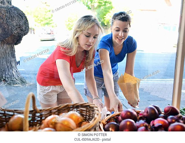 Two young women choosing food at market stall