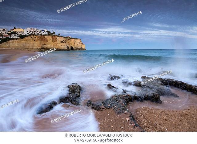 Ocean waves crashing on rocks and beach surrounding Carvoeiro village at sunset Lagoa Municipality Algarve Portugal Europe