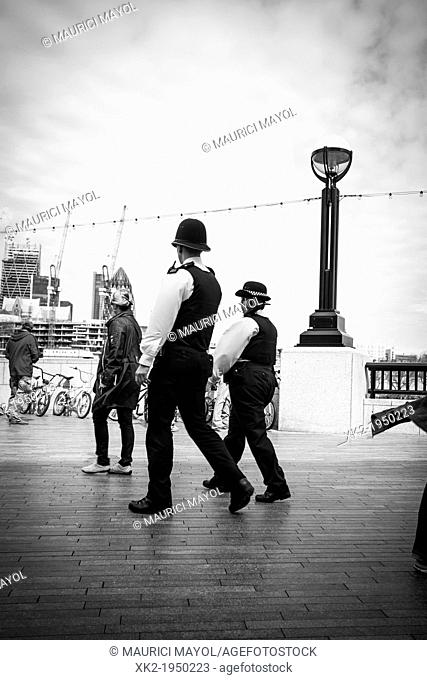 Policeman and policewoman patrol London, near city hall in Thames river path