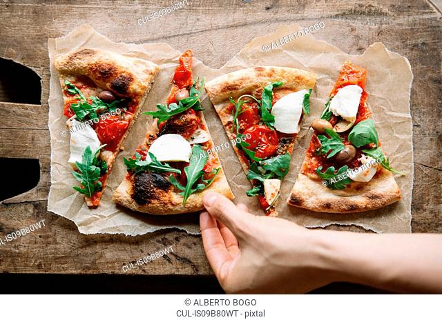 Woman taking pizza slice from chopping board, overhead view