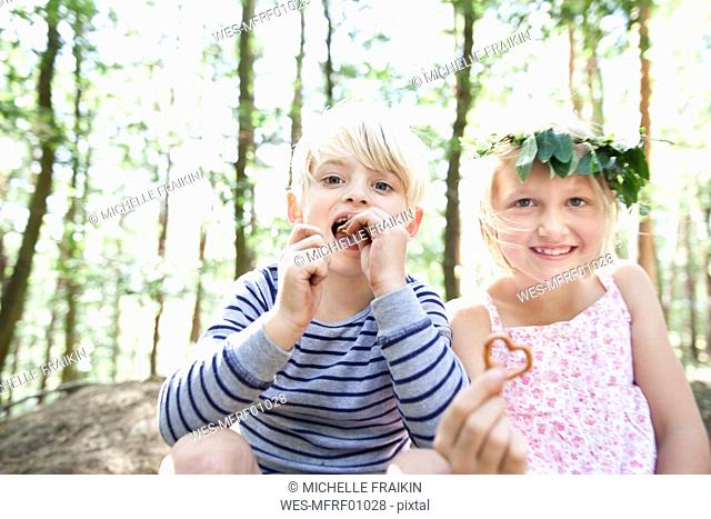Boy and girl in forest eating heart-shaped pretzel pastry