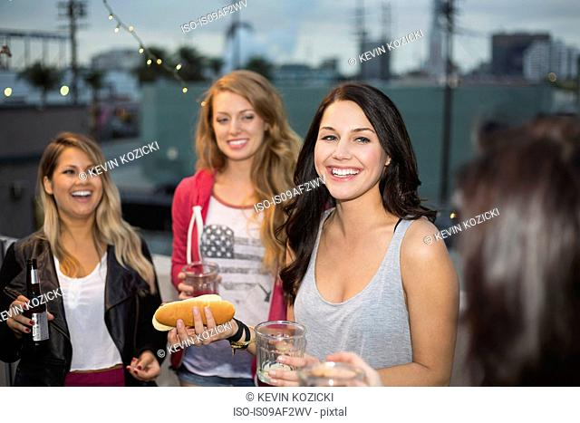 Female friends enjoying food at rooftop barbecue