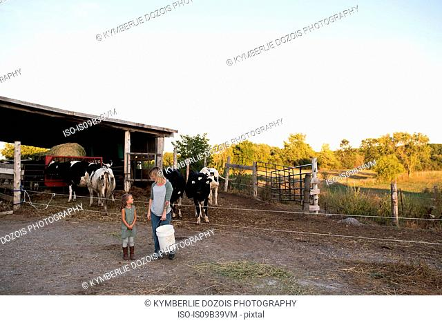 Mother and daughter standing together on farm, holding animal feed