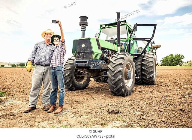 Farmer and teenage grandson taking smartphone selfie next to farm tractor