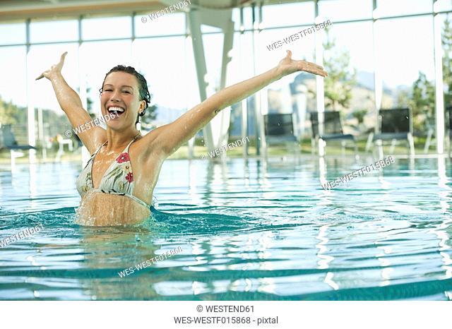 Italy, South Tyrol, Woman enjoying in swimming pool of hotel urthaler, smiling