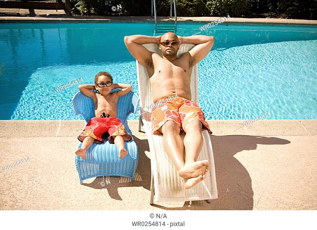 Father and son relaxing by pool