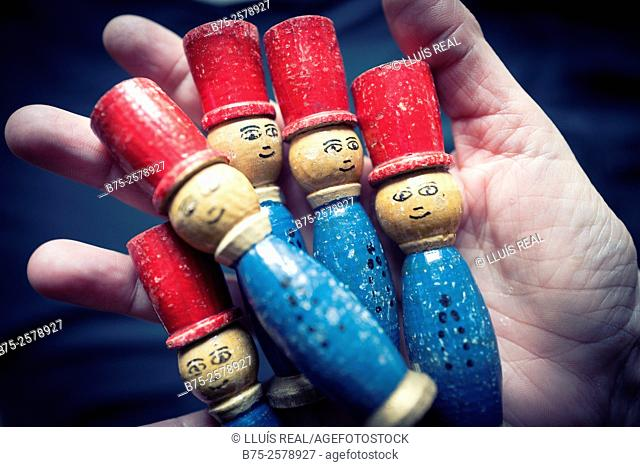 Hand with five vintage wooden dolls game of a child looking at the camera
