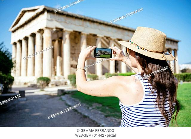 Greece, Athens, woman taking a cell phone pictire of the Hephaisteion in the Agora