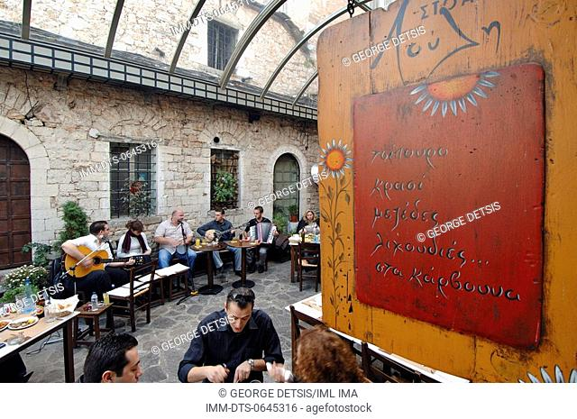 People eating in the restaurant, Stoa Louli, whilst a small band plays music. Ioannina, Epiros, Greece, Europe