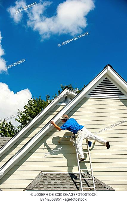 A 45 year old man on a ladder balancing on one leg clowning around while painting a house