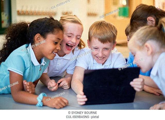 Schoolboys and girls laughing at digital tablet in classroom at primary school