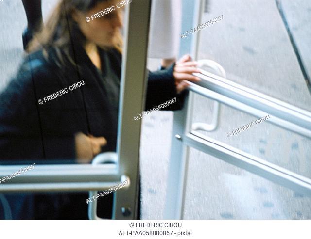 Woman opening door, blurred