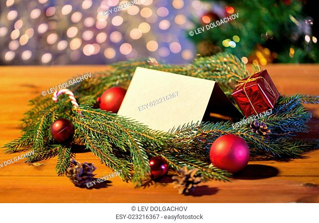 christmas, decoration, holidays, greeting and advertisement concept - close up of natural green fir branch wreath with white blank paper sheet and decorations...