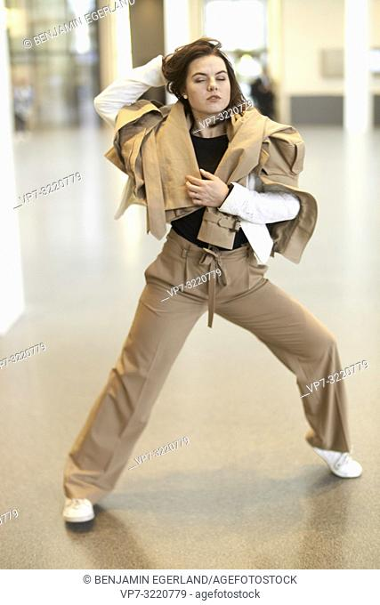 fashionable sensual woman dancing indoors, wearing new stylish fashion clothes, closed eyes, pensive thoughtful emotion, in Munich, Germany