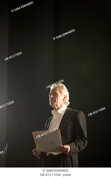 Calm orchestra conductor holding sheet music with eyes closed