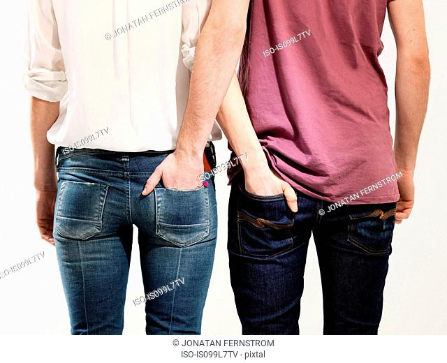 Couple with hands in each other's pockets, studio shot