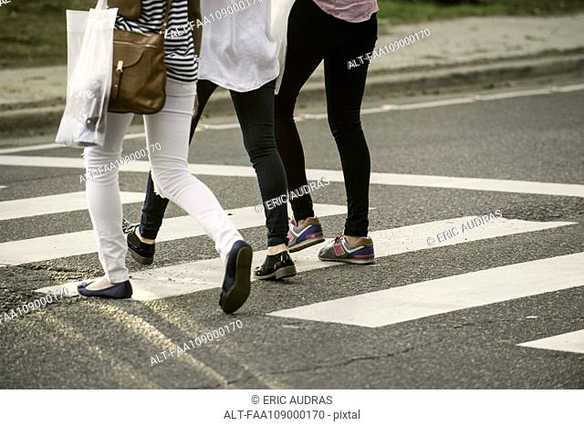 Women walking in crosswalk, low section