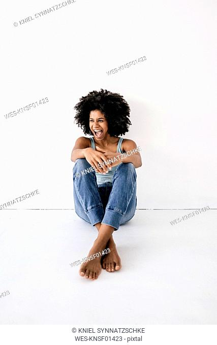 Young woman sitting on floor, laughing