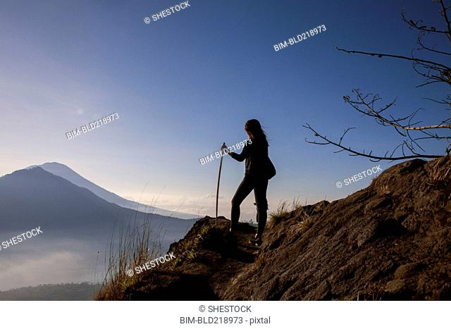 Woman admiring rural landscape from mountain path
