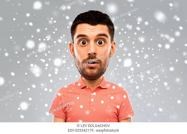emotion, facial expression, winter, christmas and people concept - surprised man in polo shirt (funny cartoon style character with big head) over snow on gray...
