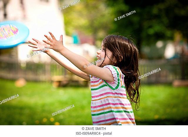 Young girl throwing frisbee in garden