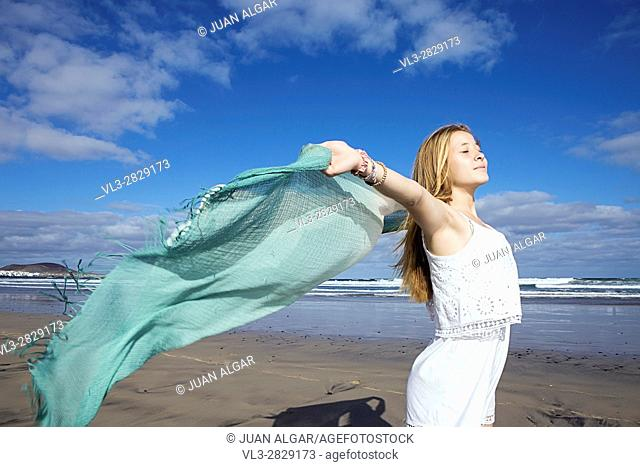 Happy young woman with beach wrap running at the seacoast. Horizontal outdoors shot