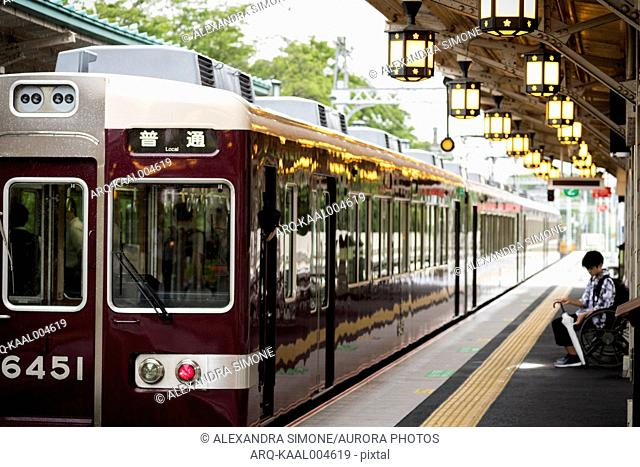 View of train departing off platform and boy with white umbrella in Arashiyama outside of Kyoto, Japan