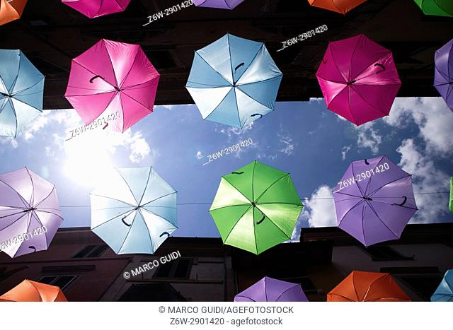 A series of umbrellas of different colors hung with a steel wire