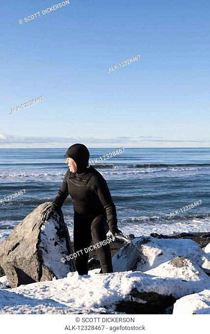 Female surfer in a wetsuit walking among the rocks and snow on the Homer Spit shoreline in winter, South-central Alaska; Homer Spit, Alaska