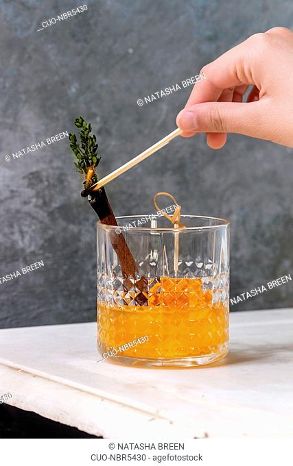 Glass of Scotch Whiskey orange juice alcohol cocktail with swirled orange peel on skewer, thyme and cinnamon sticks set fire to match
