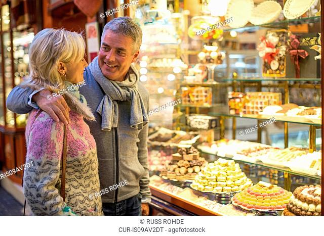 Romantic mature couple at cake shop window, Majorca, Spain