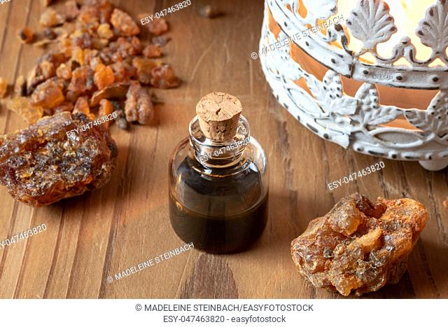 A bottle of essential oil with myrrh resin and an aroma lamp
