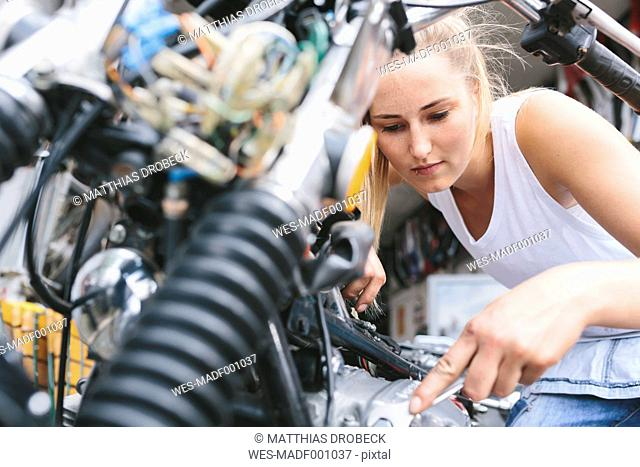 Young woman examining motorbike