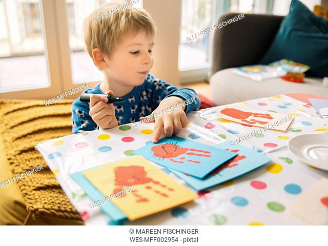 Little boy creating Easter cards with handprints at home