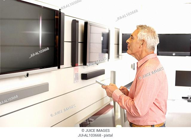 A mature man looking at televisions in a shop