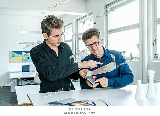 Two designers discussing workpiece in their studio