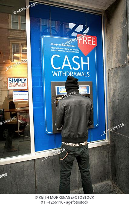 A man withdrawing cash from an Nationwide Building Society ATM
