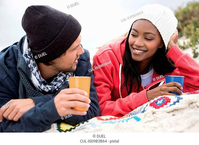Young couple picnicking and chatting on beach, Western Cape, South Africa