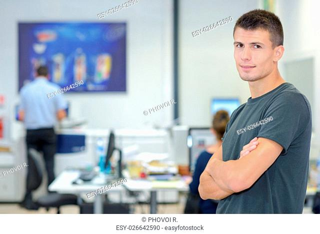Young man with arms crossed in computer room